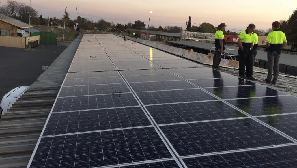 PROINSO's solar installers standing beside solar panels