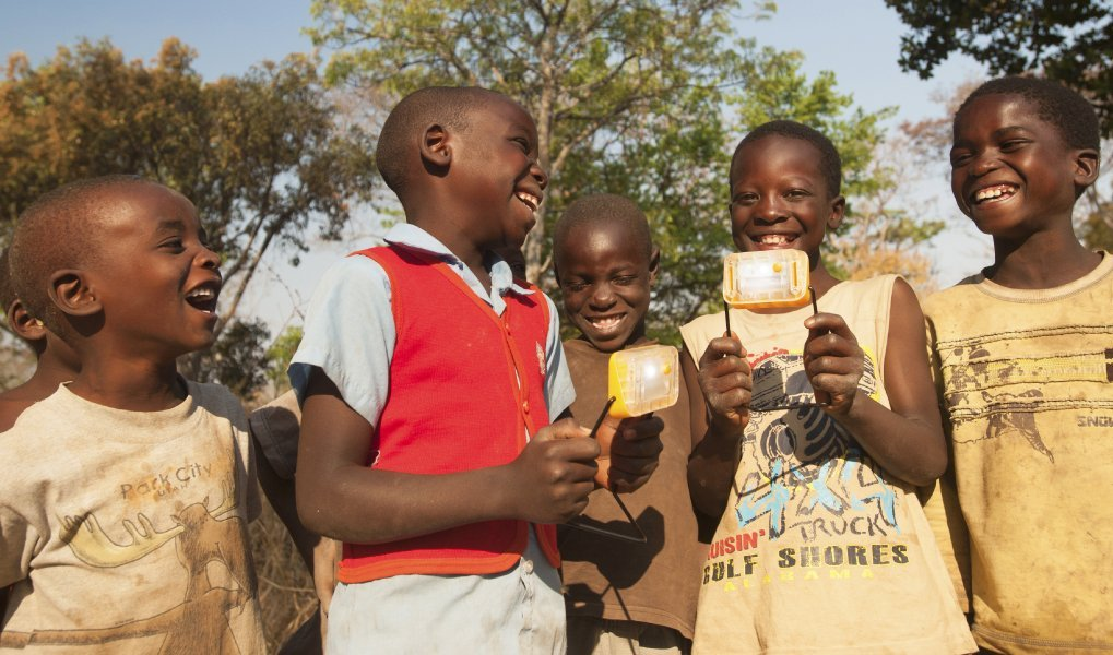 Boys in the off-grid community are smiling because they can use solar power